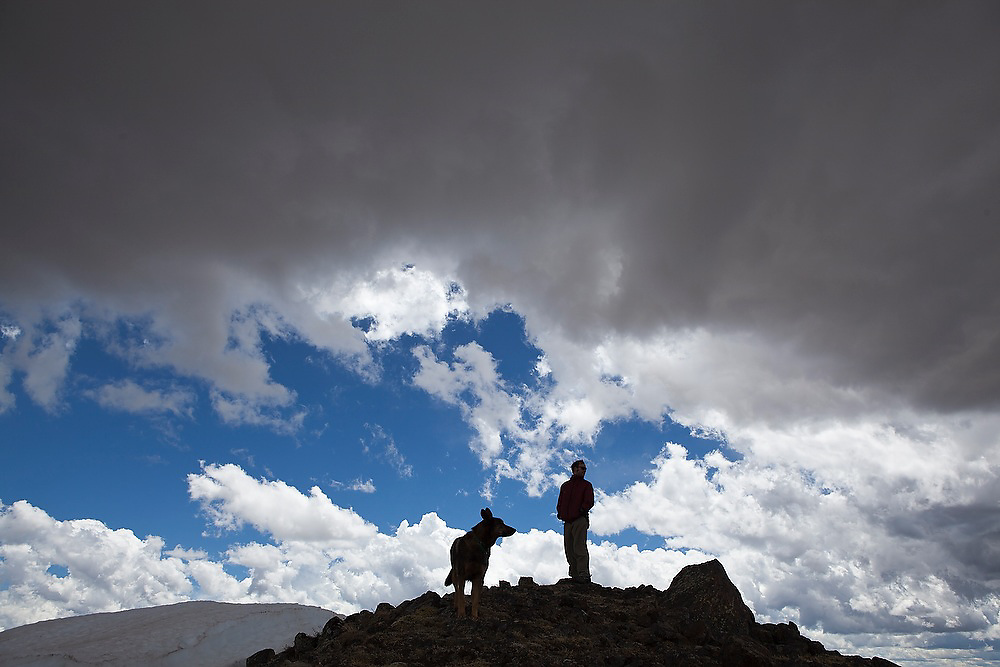 Charlie Bloch stands with his dog on the summit of Paprika Peak, Never Summer Wilderness, Colorado.