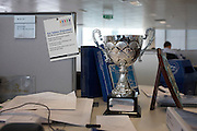 Office worker's cluttered desk with trophy, shield and company statement at an auditing company's London headquarters