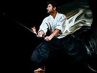one caucasian bodoka fighters man practicing Iaido  Kenjutsu studio shot isolated on black background