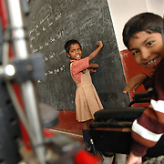 Prema (7) draws on the black board in the class room as Monsoor (7) watches from his wheel chair. She suffers from a light case of cerebral palsy (CP) in her left hand and her hearing is impaired. Monsoor also suffers from CP but needs a wheel chair to move about.