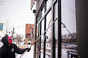 08 FEBRUARY 2021 - DES MOINES, IOWA: A window washer cleans windows outside a restaurant in downtown Des Moines. He said cut the water with an environmentally safe deicing agent but that it was so cold it wasn't working, and the water was freezing on contact with the glass. Central Iowa, including Des Moines, is enduring its coldest winter in 25 years. Daily high temperatures this week are not expected to go above 10F (-12C) and nightly lows are expected to be about -5F (-20C). In addition to the cold weather, this is the second snowiest winter in Des Moines history. So far this winter there has been more than 44 inches (111 centimeters) of snow. Des Moines normally gets about 35 inches (90 centimeters) of snow all winter.      PHOTO BY JACK KURTZ
