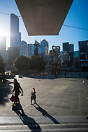 A woman and young girl cast shadows as they walk through Queensbridge Square in the CBD of Melbourne, Australia. (August 31, 2017)