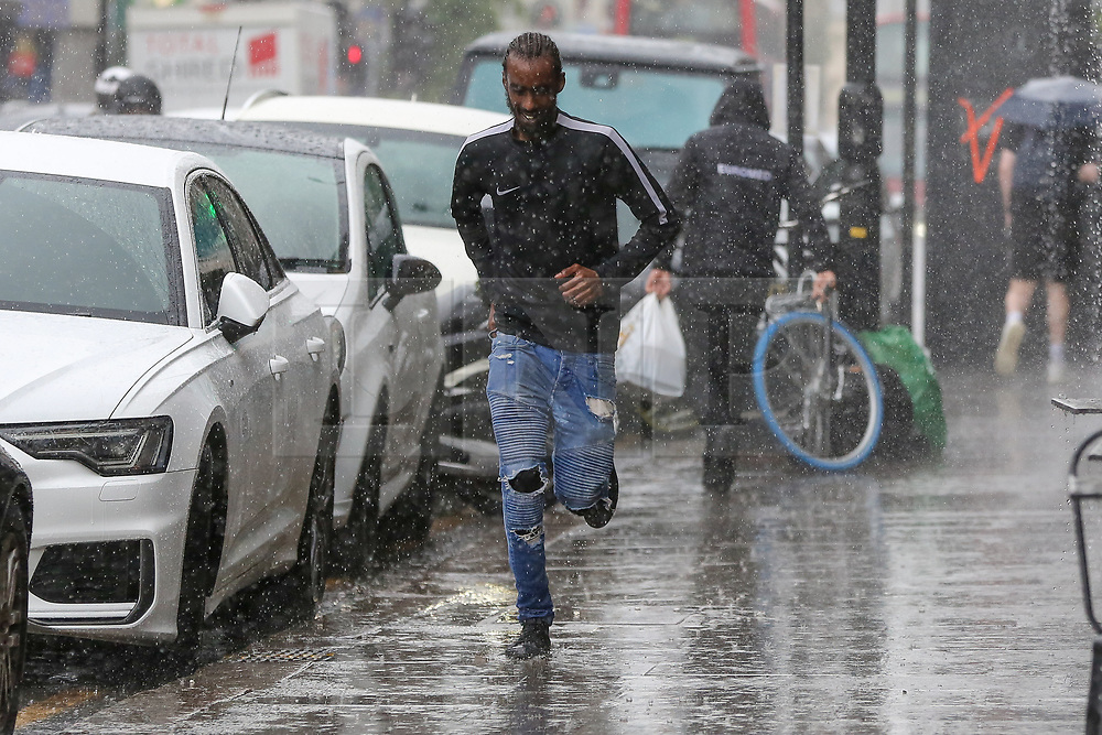 © Licensed to London News Pictures. 28/07/2021. London, UK. A man is seen running for cover during a torrential downpour in north London. According to The Met Office, wet weather is expected in the capital for this week. Photo credit: Dinendra Haria/LNP