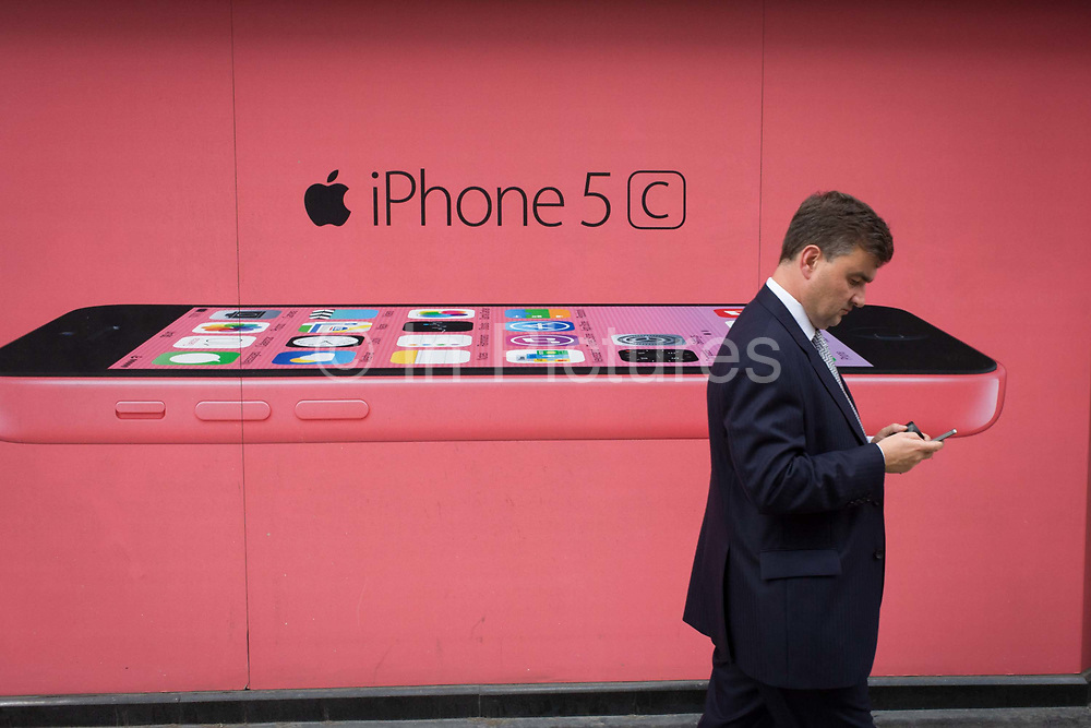 A woman walks past a phone network supplier's ad for the Apple iPhone 5c. A side profile view of the newest in the iPhone range is featured against a pink background colour, perhaps appealing more to the female buyer. A male consumer passes-by holding his own smartphone, maybe not a iPhone but one with a similar OS. The iPhone 5S (marketed with a stylized lowercase 's' as iPhone 5s) is a smartphone developed by Apple Inc. It is part of the iPhone line, and was released on September 20, 2013.