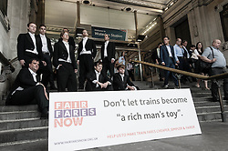 © Licensed to London News Pictures. 14/08/2012. London, UK.   London, UK.  A protest against rising train fares, organised by Fair Fares Now, and held outside Waterloo Rail Station.   The protesters are dressed as members of the Bullingdon Club,  an exclusive members-only club known for having George Osbourne, UK Chancellor of the Exchequer.  This coincides with the release of July inflation figures which determines how much the increase will be for 2013.  Another protest was held alongside it simultaneously by the TUC.   Photo credit : Richard Isaac/LNP