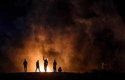 © Licensed to London News Pictures. 23/10/2016. Calais, France. A group of young migrants taunt the French police as they fire tear gas at groups of migrants at the 'Jungle' camp in Calais, on the eve of the demolition of the camp. French authorities have given an eviction order to thousands of refugees and migrants living at the makeshift living area of the French coast. Photo credit: Ben Cawthra/LNP
