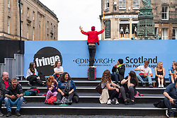 Edinburgh, Scotland, UK. 6th August  2021.  Images from the Royal Mile in Edinburgh Old Town on the opening day of the Edinburgh Fringe Festival 2021.  The festival looks very different from two years ago . Very few street performance spaces are permitted and far fewer tourists are evident. Also a high police visibility, there are more police officers than performers on the street, is in marked contrast to previous years. Pic; Street performer in panic trying to alert public to start of his show in screened off area which is not obvious to passerby. Iain Masterton/Alamy Live news.