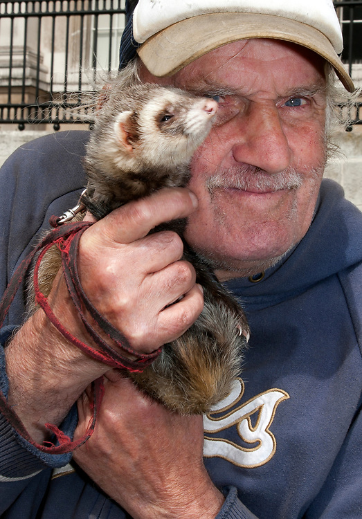 Elderly man with his pet ferret on a lead, London, UK