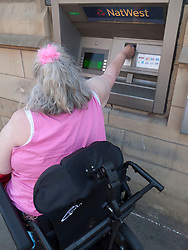 Wheelchair user using bank cash point..(Not cleared for newspaper and television use)