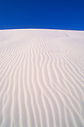 Morning light on dune patterns in gypsum sand under blue sky, White Sands National Park, New Mexico