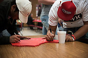 The Iraan High School football team signs a gift during a community dinner in Iraan, Texas on December 13, 2016. (Cooper Neill for The New York Times)