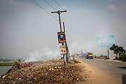 A man searches through a burning rubbish pile next to the N305 highway and the banks of the Turag river on the 1st of October 2018 in Dhaka, Bangladesh. Environmental pollution next to rivers and lakes is a common sight in Dhaka, polluting water sources that also used for washing and drinking water.  (photo by Andrew Aitchison / In pictures via Getty Images)