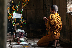 Aug. 2, 2013 - Young Buddhist monk praying inside temple in Angkor Wat, Siem Reap, Cambodia (Credit Image: © Gary  Latham/Cultura/ZUMAPRESS.com)