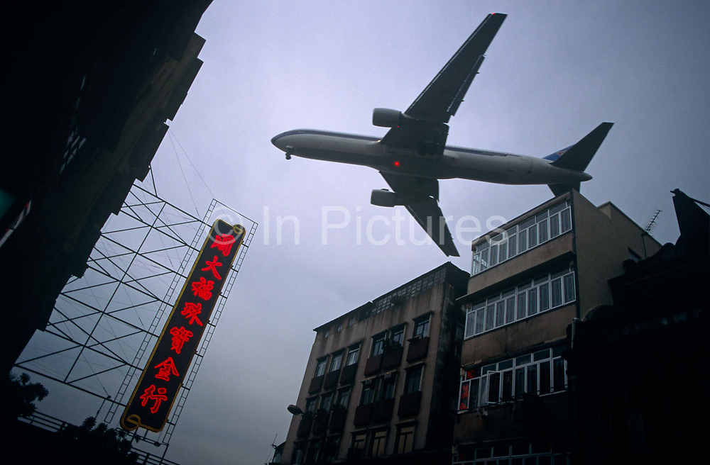 On a grey day in the metropolis of Hong Kong, a giant airliner belonging to an Asian airline passes overhead, seemingly just over the roofs of apartment buildings and offices. The aircraft is nearly at the point of touching down on the runway which is just beyond this street in Kowloon district in the days when Hong Kong was still a British colony and before its handover to Chinese law. The dominating shape of the jet is flying into the former airport called Kai Tak whose runway jutted out into the city's harbour before the airfield was closed and a new location was opened in an outlying island. We look up to see a wide expanse of overcast sky with the red vertical Cantonese characters of a local business and which echoes the red beacon on the plane's belly that flashes during the last moments of flight before the actual landing.