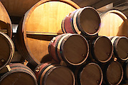 "Wooden barrels with aging wine in the cellar of Guigal in Ampuis. The barrels are stored ""bond a cote"" (with the bung hole to the side - slightly to the left in this case), a methid favoured by some wine producers because it supposedly leads to less evaporation and less risk for oxidation.  Domaine E Guigal, Ampuis, Cote Rotie, Rhone, France, Europe"