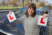 A young 23 year-old woman celebrates the passing of her driving test by holding up her L Plates in front of the family car in south London, on 7th December 2018, in London England.