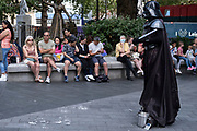 With many people and families staying in the UK for their Summer break during the school holidays, a large number of domestic tourists, who may normally have been travelling abroad, have decended on the capital to see the sights, as seen here in Leicester Square as a Darth Vader awaits tourists to be photographed with on 10th August 2021 in London, United Kingdom. Following the Coronavirus / Covid-19 health scare of the last two years, and with some travel restrictions still in place, more people have chosen a staycation which is a holiday spent in ones home country rather than abroad, or one spent at home and involving day trips to local attractions.