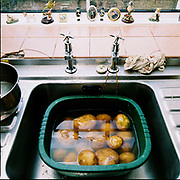 Potatoes waiting to be peeled in a green washing-up bowl in the kitchen sink of Warren Farm, Exmoor, Somerset, UK