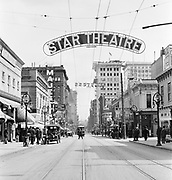 """9120-07. SW Washington at Park Ave, looking east.  This is the core of Portland's Theatre district as it was in 1911.  The intersection one block in the background is Portland's main intersection from that era, 8th Ave. (now Park).  The Star Theatre, on the extreme left, is now O'Bryant Square.   On the right is Cordray's Theatre, in it's later days when it was known as the Empress and the Grand.  The heyday of these theatres was from 1900 to 1910, when Portland's population more than doubled and good crowds supported seven nights and three matinees a week.  In 1909 the Portland City Council, responding to a disastrous theatre fire in Chicago, ruled that all theatres in frame buildings must cease operations.  The April 1911 deadline doomed the theatre district, and although several new vaudeville stages were constructed in other parts of downtown, the """"stock companies"""" lost out to motion picture in the market and were all but gone by the great depression.  The building in the background under construction is the Wilcox building, built 1911"""