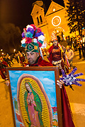 Catholic faithful dressed as Matachin warriors carry the likeness of the Virgin Mary during a procession from the Cathedral Basilica of St. Francis of Assisi celebrating our Lady of Guadalupe December 11, 2015 in Santa Fe, New Mexico. Guadalupanos as the devotees are known, celebrate the apparitions of the Virgin Mary to an Aztec peasant at Tepeyac, Mexico in 1531.
