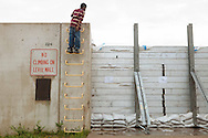 Chad Sutton, 12, looks over a levee wall holding back floodwater from the Ohio River in Cairo, Illinois.