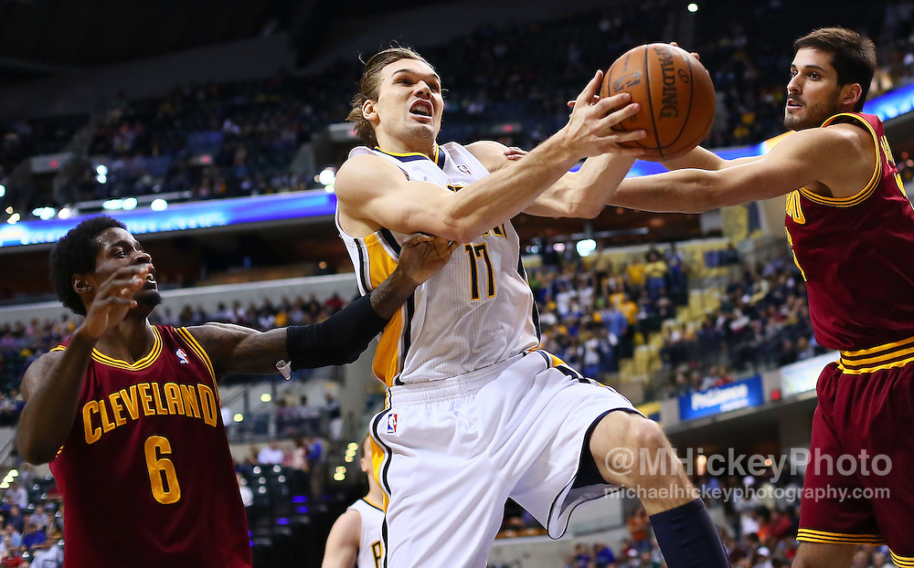 April 13, 2012; Indianapolis, IN, USA; Indiana Pacers center Louis Amundson (17) snags a rebound as Cleveland Cavaliers guard Manny Harris (6) and Cleveland Cavaliers small forward Omri Casspi (36) defend at Bankers Life Fieldhouse. Mandatory credit: Michael Hickey-US PRESSWIRE