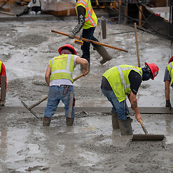Experienced concrete crews conduct an early morning concretepour with smoothing and shaping on the top floors of a high-rise parking garage in downtown Austin on Augut 22, 2020. Major construction projects continue unabated during the coronavirus shutdowns in Texas.