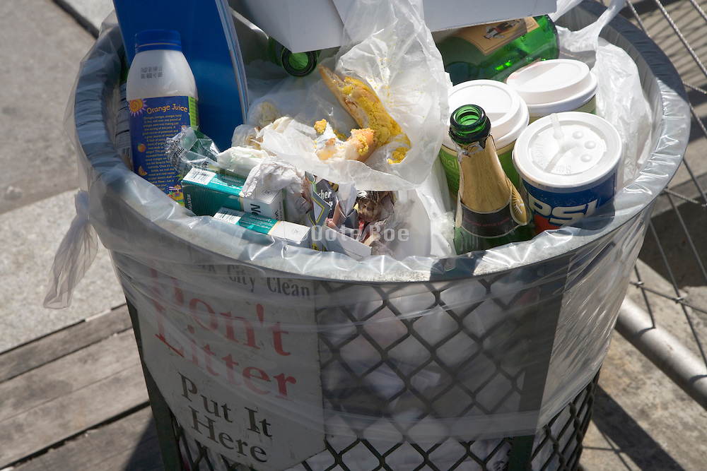 a street side garbage can filled to the top with bottles and other trash