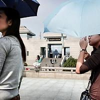 China, Xian,maart 2008..Chinese toeristen met parapluies tegen de zon met op de achtergrond 1 van de musea met opgravingen van het Terra Cotta leger.