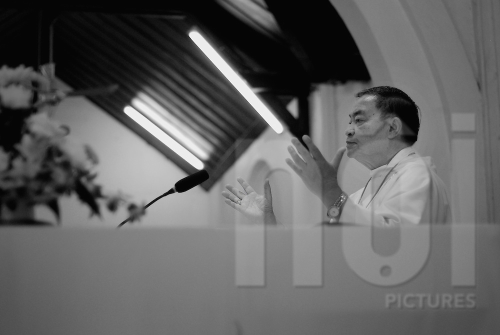 A priest preach with open arms in a church of Vientiane, Laos, Asia