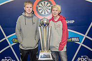 Darts fans pose next to the World Championship Trophy during the World Darts Championships 2018 at Alexandra Palace, London, United Kingdom on 19 December 2018.