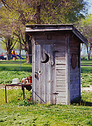 Finely crafted outhouse with cut crescent moon and 55-gallon drum lid with smiling face, Levan, Utah.