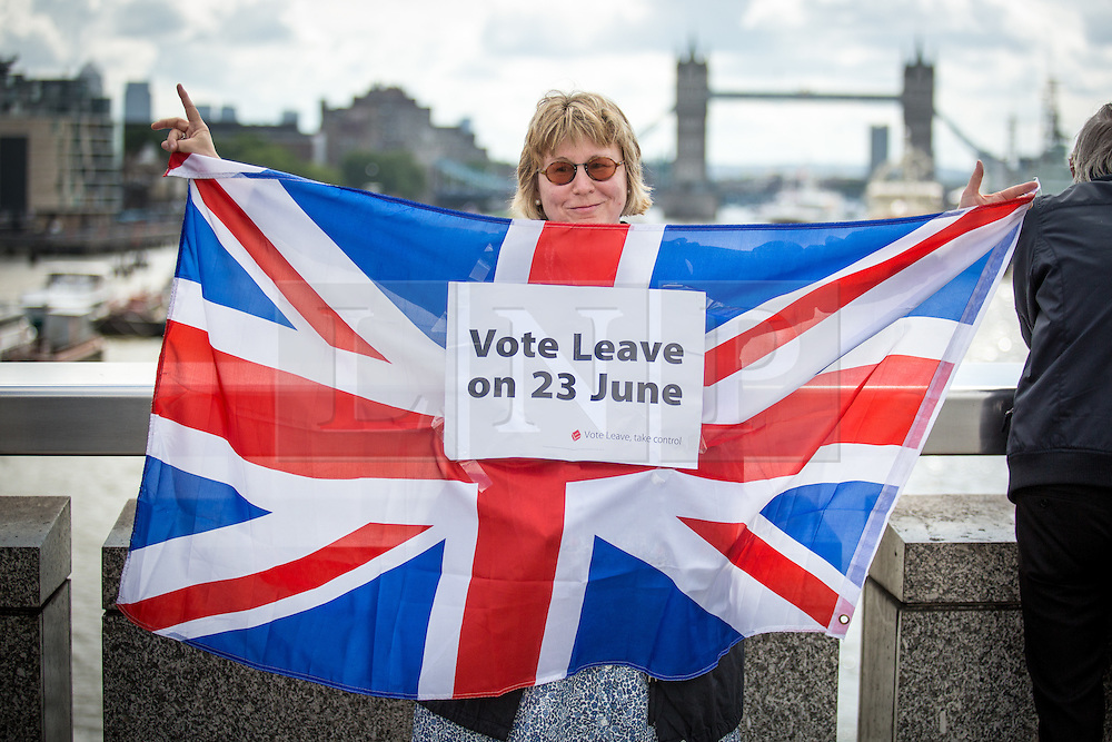 © Licensed to London News Pictures. 15/06/2016. London, UK. A campaigner holds a Union Jack flag as the pro-Brexit campaign 'Fishermen for Leave', sail a flotilla of over 30 vessels up the Thames. The flotilla, including UKIP leader Nigel Farage, caused traffic issues in central London, as vessels travelled up the Thames for high tide and to coincide with the last Prime Minister's Questions before the EU referendum takes place on 23 June. Photo credit : Tom Nicholson/LNP
