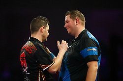 Kevin Munch (right) congratulates Toni Alcinas on his victory during day eleven of the William Hill World Darts Championship at Alexandra Palace, London.
