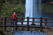 USA, Oregon, Silver Falls State Park,  South Falls, hiker looking at South Falls from foot bridge on Canyon Trail, MR