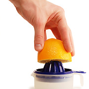 Orange squeezer with hand holding half of an orange