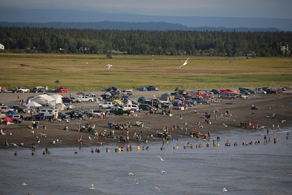 Alaska; Scenic of Kenai River dipnetters oalong the south shore of the Kenai River, along with the circus of vehicles, people and tents. with Mt. Redoubt volcano in the background.