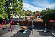 Childrens swings can be seen in the foreground as a  digging machine is used on a demolition site in close proximity to a childrens playground in London, United Kingdom on 13th September 2019.