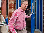 11 MAY 2019 - DAVENPORT, IOWA: JOHN HICKENLOOPER, the former Governor of Colorado, walks over sandbags and water barriers in a flooded neighborhood of Davenport. Downtown Davenport experienced its worst flooding in more than 20 years this year. Gov. Hickenlooper met with voters in Davenport Saturday. He is campaigning in Iowa this weekend to be the Democratic party's nominee for the US Presidency. Iowa traditionally hosts the the first election event of the presidential selection cycle. The Iowa Caucuses will be on Feb. 3, 2020.          PHOTO BY JACK KURTZ