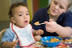 Nursery nurse feeding a hungry nursery school girl,