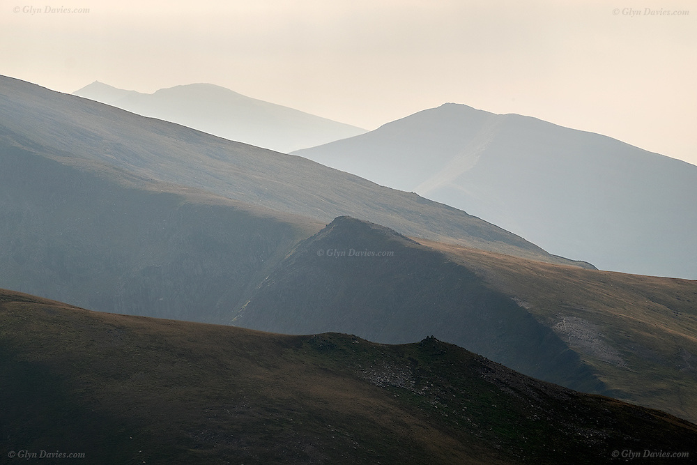 View south over the misty Carneddau mountains and Mynydd Du, over to Elidir Fawr and finally the pointed summit of Snowdon in the far distance.