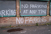 No parking sign painted on a wall and shutters to prevent pavement parking in Balsall Heath on 24th November 2020 in Birmingham, United Kingdom. Birmingham has become a city where locals say that a certain ireesponsibility has developed, where drivers show little respect for the law, and seem to want to park anywhere they choose.