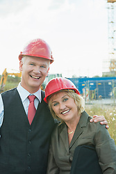 Businesspeople on site wearing safety helmets