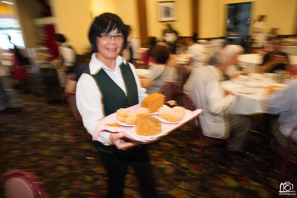A server showcases dessert plates at Great Mall Mayflower Restaurant in Milpitas, California, on September 11, 2014. (Stan Olszewski/SOSKIphoto)