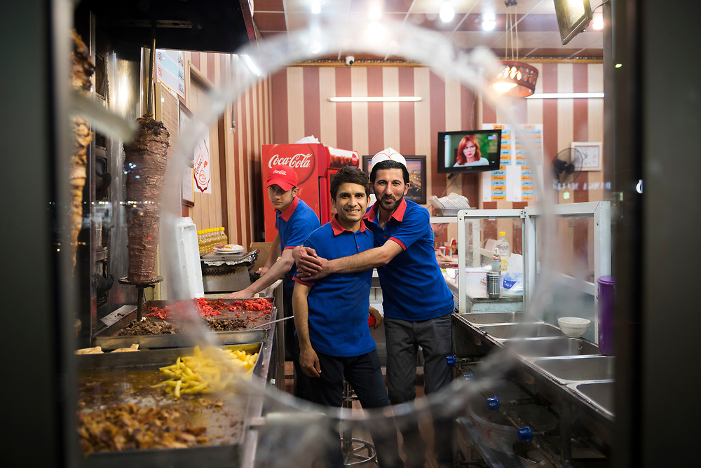 Muhamed, on the right and from Anbar, and Khalid, in the center and from Mosul, work at a restaurant in Erbil, Iraq. (May 4, 2017)
