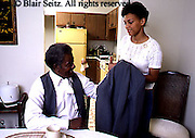 Active Aging Senior Citizens, Retired, Activities, Adult African Daughter Helps Father with Coat