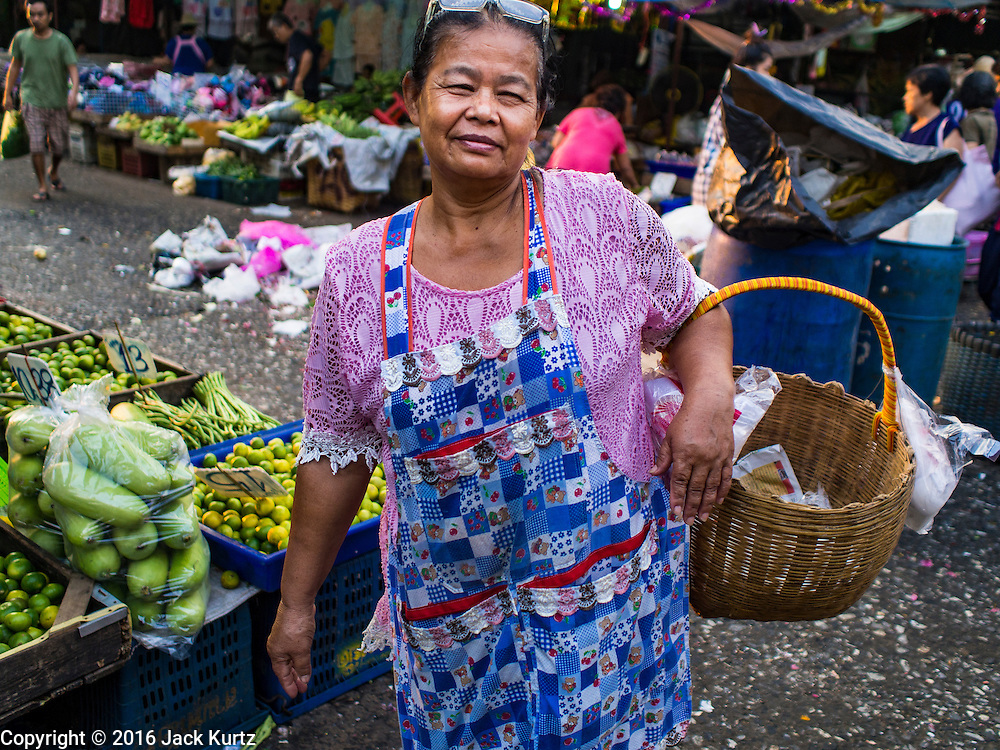 """12 JANUARY 2016 - BANGKOK, THAILAND: A shopper in Khlong Toey Market in Bangkok. Khlong Toey (also called Khlong Toei) Market is one of the largest """"wet markets"""" in Thailand. The market is located in the midst of one of Bangkok's largest slum areas and close to the city's original deep water port. Thousands of people live in the neighboring slum area. Thousands more shop in the sprawling market for fresh fruits and vegetables as well meat, fish and poultry.         PHOTO BY JACK KURTZ"""