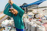 """28 MARCH 2014 - NA KHOK, SAMUT SAKHON, THAILAND: A Burmese migrant laborer holds up a tent that shelters workers on a Thai salt farm in Samut Sakhon province. Thai salt farmers south of Bangkok are experiencing a better than usual year this year because of the drought gripping Thailand. Some salt farmers say they could get an extra month of salt collection out of their fields because it has rained so little through the current dry season. Salt is normally collected from late February through May. Fields are flooded with sea water and salt is collected as the water evaporates. Last year, the salt season was shortened by more than a month because of unseasonable rains. The Thai government has warned farmers and consumers that 2014 may be a record dry year because an expected """"El Nino"""" weather pattern will block rain in mainland Southeast Asia. Salt has traditionally been harvested in tidal basins along the coast southwest of Bangkok but industrial development in the area has reduced the amount of land available for commercial salt production and now salt is mainly harvested in a small parts of Samut Songkhram and Samut Sakhon provinces.    PHOTO BY JACK KURTZ"""