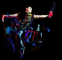 wushu chinese boxing kung fu Hung Gar fighter isolated man isolated on black background with speed light painting effect motion blur