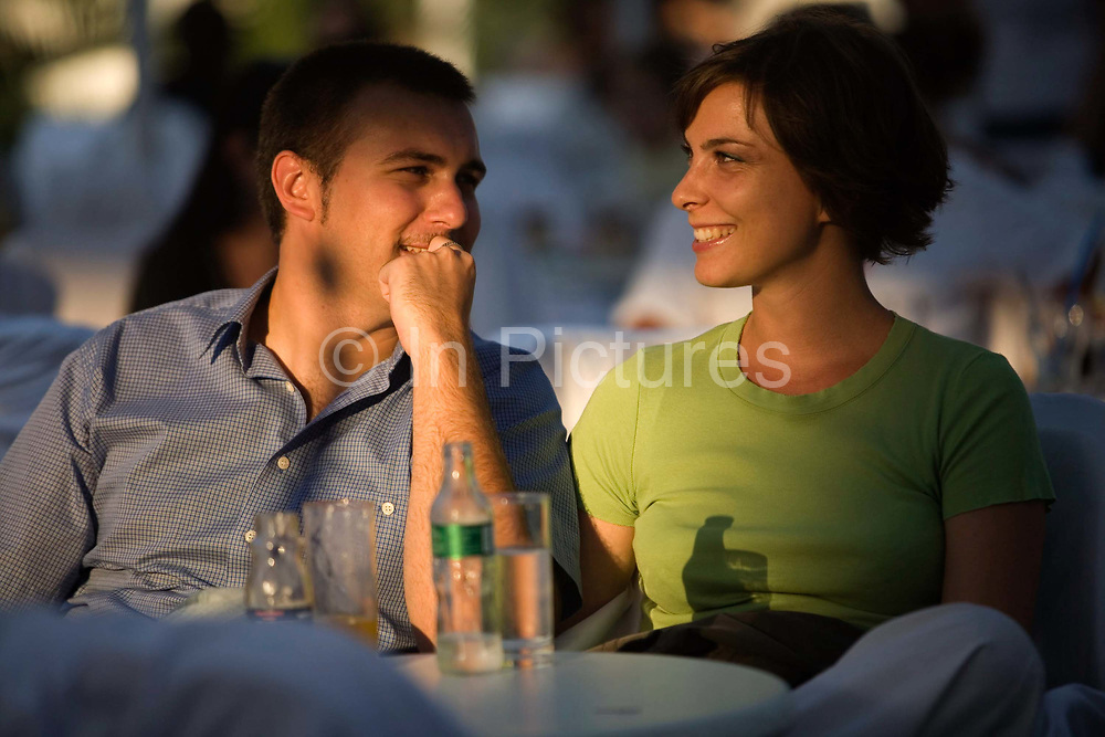 A couple enjoy drinks at a cafe in the late afternoon sun at the Sarajevo Film Festival, Sarajevo, Bosnia